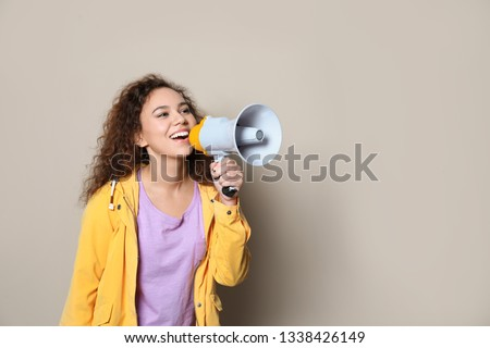 Young African-American woman with megaphone on color background. Space for text #1338426149