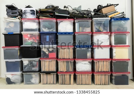 Tall wall of plastic file storage boxes with folders, binders and miscellaneous business office supplies.   #1338455825
