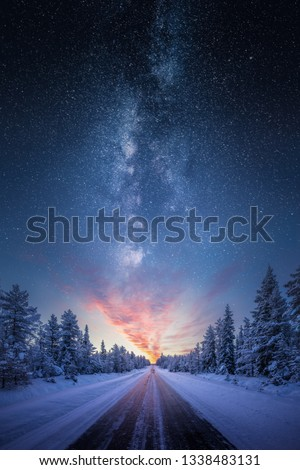 Road leading towards colorful sunrise between snow covered trees with epic milky way on the sky #1338483131