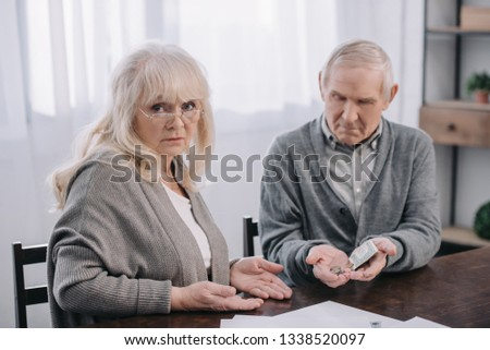 senior couple in casual clothes sitting at table and holding money in hands #1338520097