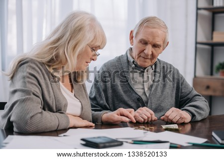 senior couple in casual clothes sitting at table with paperwork while counting money #1338520133
