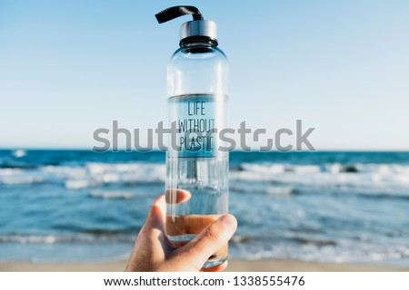 closeup of a caucasian man holding a glass reusable water bottle with the text life without plastic written in it, on the beach, with the ocean in the background Royalty-Free Stock Photo #1338555476