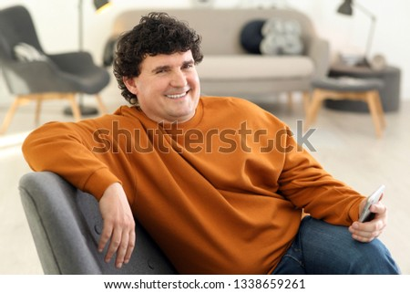 Mature man with mobile phone at home #1338659261