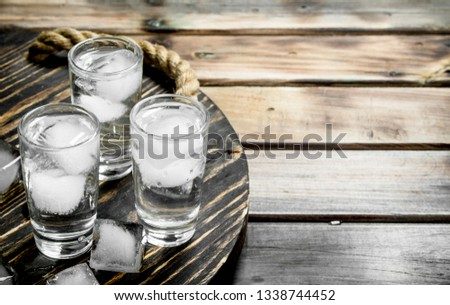 Vodka in a shot glass and ice cubes on tray. On wooden background #1338744452