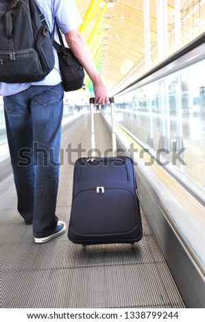 Traveler with a suitcase on the speedwalk #1338799244