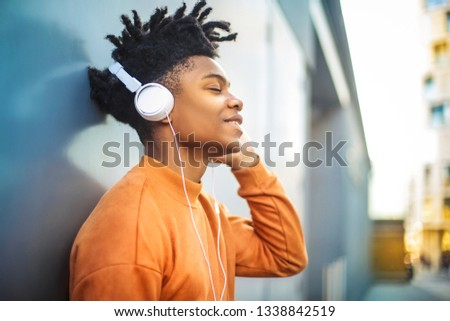 Cheerful guy listening music with the headphones #1338842519