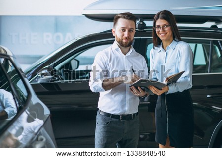Salesman and woman looking for a car in a car showroom #1338848540