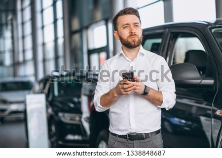Business man using phone in a car showroom #1338848687