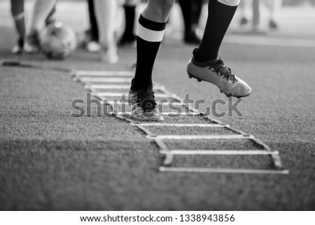Black and white picture of Young boy soccer players Jogging and jump between ladder drills for football training.