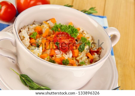 Delicious rice with vegetables and herbs in pot on wooden table close-up #133896326