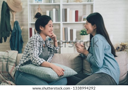 Two asian casual women relaxing on sofa with hot drink in new home. young girls chatting talking about funny things gossip laughing on couch in apartment. female roommates stay in dormitory together. #1338994292