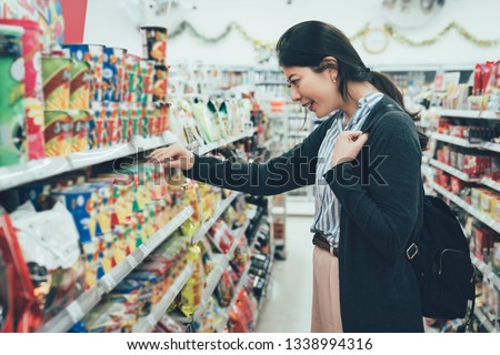 sale shopping consumerism people concept. asian woman backpacker with curious face picking snack cookies choose at grocery supermarket. lady buying products food instant noodles in convenience store. #1338994316