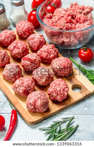 Raw beef meatballs with herbs and spices. On a rustic background. #1339063316