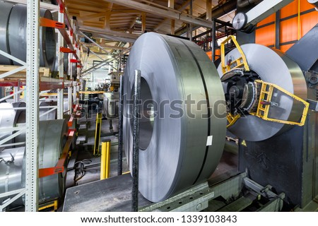 Cold rolled steel coil on decoiler of machine in metalwork manufacturing. Modern equipment for sheet metal processing. #1339103843