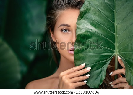 Luxury Portrait of a Beautiful  young woman with natural makeup holds a  big green leaf on a  blurred green background. Spa and wellness. Youth, teens and skin care concept. Close up #1339107806