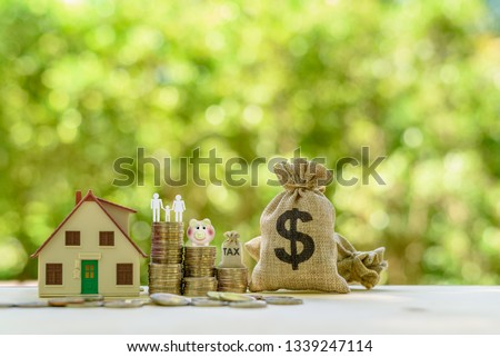 Money saving, first time asset / property buyer concept : Family couple, home model, piggy bank, dollar and tax bags, stacks of rising coins, depict budget planning for basic needs, personal expense. #1339247114