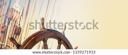 Steering wheel and marine ropes on the old ship for your concept of marine voyage under sails. Nautical equipment on ancient sailing vessel with a wooden wheel of captain. #1339271933