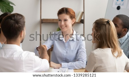 Smiling businesswoman shaking hand of colleague at briefing, team leader congratulating subordinate with promotion, thanking for good work results, greeting business partner, successful negotiations #1339285121
