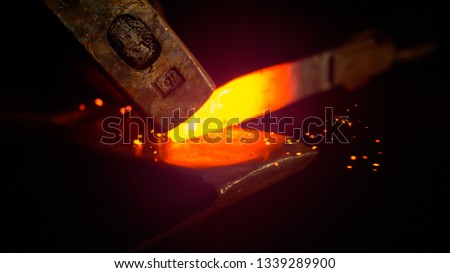 MACRO, DOF: Small black particles flying away from hot red blade while getting forged by an unrecognizable blacksmith. Glowing piece of iron being forged into blade. Person forging knife blades. #1339289900