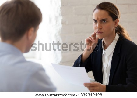 HR manager looking suspiciously at job candidate reading cv resume of male applicant. Skeptic woman is unpleasantly surprised by no good results. Bad first impression, reject View over the shoulder #1339319198