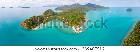 Tropical landscape aerial panorama with island coastline and beaches surrounded by transparent blue sea water, green rainforest, panoramic view from drone, summer vacation holidays destination #1339407512