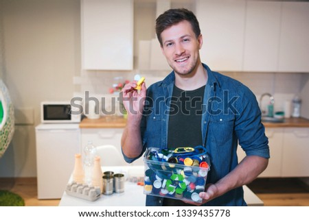 Protect the environment. Plastic lids prepared for recycling. Young smiling man holding recycling container filled with bottles lids on kitchen background #1339435778