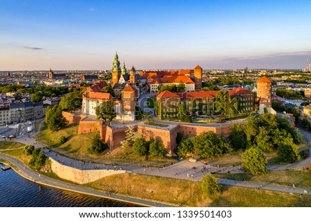 Poland. Krakow skyline with Wawel Hill, Cathedral, Royal Wawel Castle, defensive walls,Vistula riverbank, park, promenade, walking people. Old city in the background #1339501403