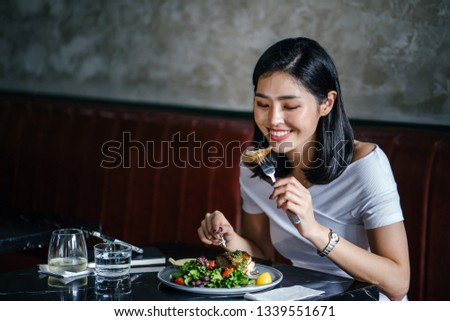 Portrait of a beautiful Korean Asian woman smiling as she enjoys a tasty and healthy salad in a trendy cafe or restaurant during the day on her own. She is gorgeous, elegant and is enjoying her meal. #1339551671