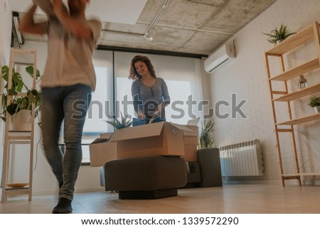 Happy young couple unpacking or packing boxes and moving into a new home. #1339572290