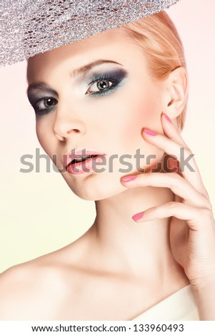 Beautiful woman face with blue makeup and leaf on a pink and yellow background #133960493