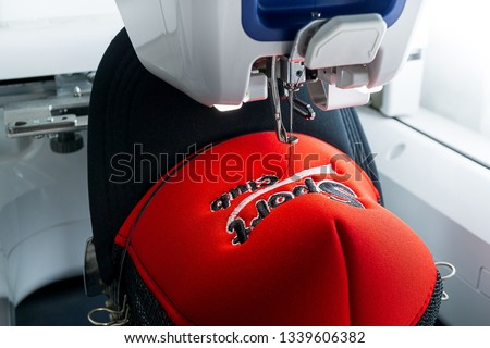White Embroidery machine and red and black sport cap on the hoop, close up picture