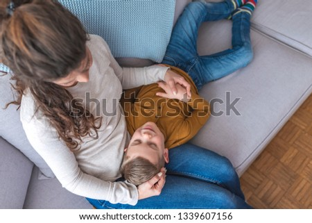 Adorable Little Boy Asleep on Mothers Laps. Close up of Cute Little Son Sleeping on Moms Laps. Young Woman Sitting on Sofa with Sleeping Child. Family Parenthood Concept #1339607156