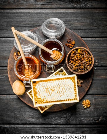 Assortment of different types of honey. On a wooden background. #1339641281