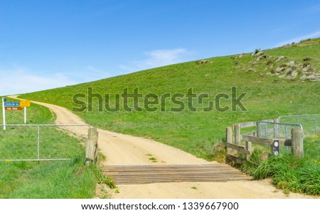 Dirt road through farmland over cattle stop and past direction signs