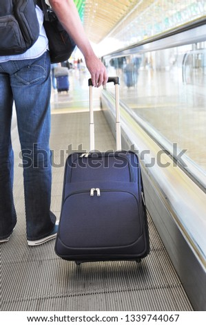 Traveler with a suitcase on the speedwalk #1339744067