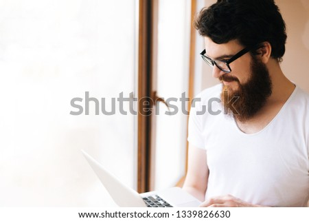 Handsome  bearded man. Attractive freelancer using laptop near window at home #1339826630