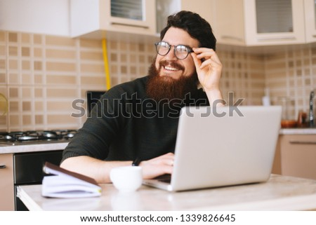 Young man with beard working on laptop. Smiling student is looking away thinking about something funny in kitchen at home. #1339826645