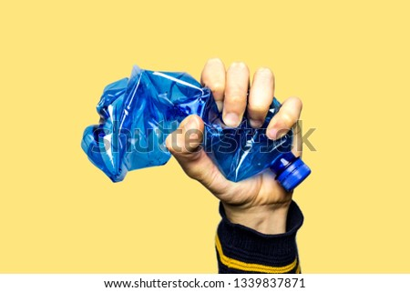 Concept of stop plastic pollution, global warming, recycling plastic, plastic free. Hand tightly squeezes an empty blue plastic bottle in a sign of protest. Yellow background with an isolated subject