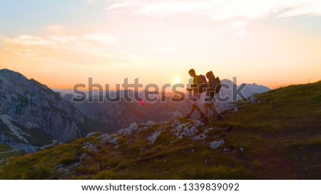 DRONE, LENS FLARE: Active young woman and boyfriend descending down the mountain at sunrise. Tourist couple enjoying a summer vacation by hiking high in the Alps on a sunny evening. Trekking at sunset #1339839092