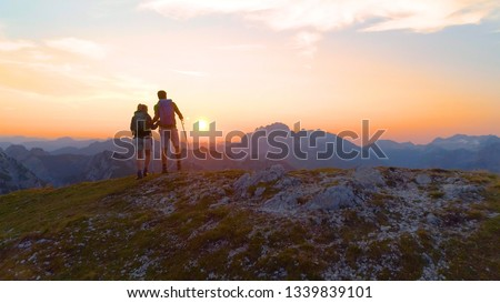 AERIAL, SUN FLARE: Unrecognizable hiker couple observes the breathtaking evening landscape from the mountaintop. Sporty young man and woman watches the sunrise from a peak in the serene Julian Alps. #1339839101