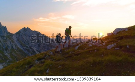 AERIAL: Active young tourists hiking up a grassy mountain in the Alps at sunset. Carefree hiker couple enjoying a relaxing evening trip in the breathtaking Julian Alps. Sporty tourists on a trek. #1339839104