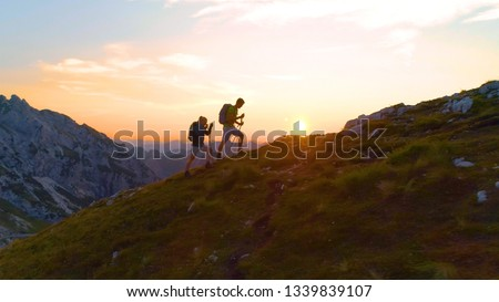DRONE, SUN FLARE: Young hiker couple enjoying a tranquil evening trip in the breathtaking Julian Alps. Carefree active man and his athletic girlfriend having fun hiking up a hill at beautiful sunrise. #1339839107