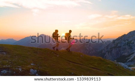AERIAL, SUN FLARE: Flying along a cheerful tourist couple hiking down a grassy hill in the picturesque Alps on a sunny summer morning. Active man and girlfriend enjoying a scenic trek at sunset. #1339839113