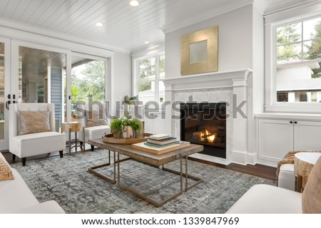 Beautiful white living room in new luxury home with white interior. Has fire in fireplace  #1339847969