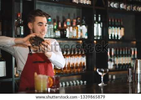 Professional bartender in uniform doing show of his work, holding two parts of metal shaker in his hands and pouring a cocktail, shelves full of bottles with alcohol on the background #1339865879
