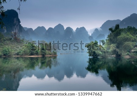 Fantastic clouds and sunset sky. Peaceful time. Colorful sky reflecting in the lake. Silhouette. Summer is coming. Beautiful peaceful scenery of mountain forest in Th.Lam Commune, T. Quang Province,VN #1339947662