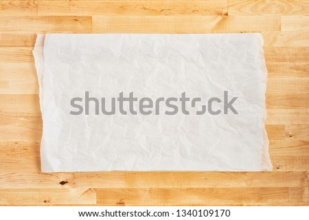 Crumpled piece of white parchment or baking paper on wooden table. Top view. Copy space for text and design element. #1340109170