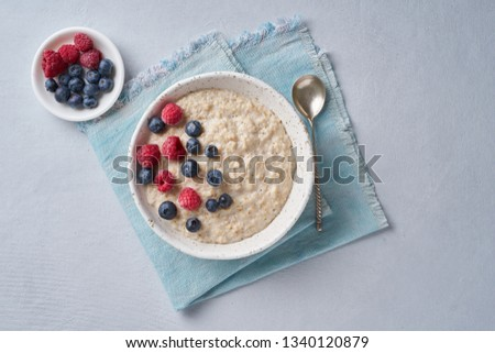 Oatmeal with blueberries, raspberries on blue light background. Top view. Healthy diet breakfast #1340120879