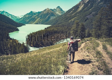 Lake with rocky ridge. Beautiful landscape. The tourist goes over the rocks on the shore of the lake. Altay Russia #1340169074