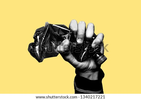 Concept of stop plastic pollution, global warming, recycling plastic, plastic free. Hand tightly squeezes an empty plastic bottle in a sign of protest. Yellow background with a black and white subject #1340217221
